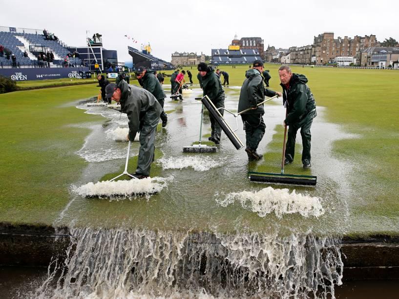 Durante o segundo dia do campeonato britânico, homens retiram água de campo de golfe após forte chuva em St Andrews, na Escócia - 17/07/2015