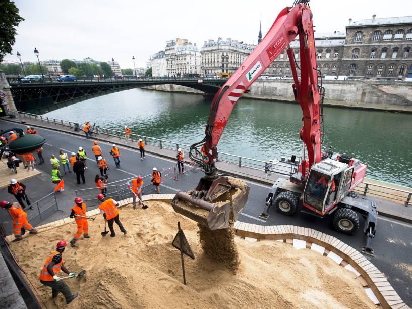 Nas margens do rio Sena, em Paris, funcionários trabalham na montagem de uma praia artificial. Com a chegada do verão, a cidade prepara uma série de praias ao longo do rio para a 14ª edição do Paris-Plages- 17/07/2015
