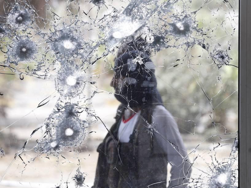 Guerrilheiro da resistência sulista é fotografado atrás de uma janela danificada enquanto monta guarda no aeroporto internacional do Iêmen - 24/07/2015