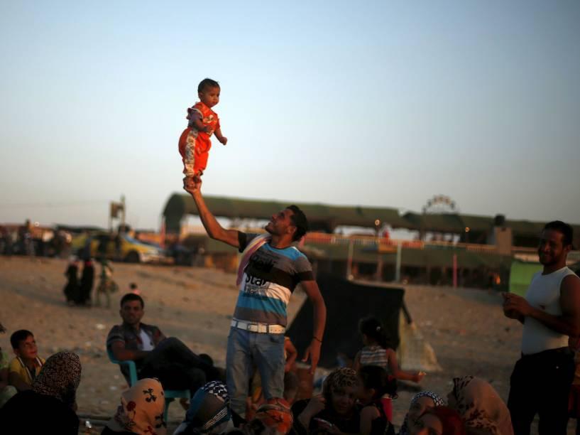 Homem palestino levanta sua filha enquanto aproveita o clima ameno em uma praia de frente ao mar Mediterrâneo, na Faixa de Gaza - 24/07/2015