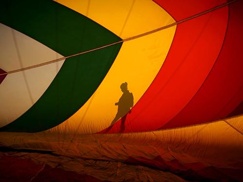 Mulher passa por balão durante festival de Balonismo em Nova Jersey, nos Estados Unidos