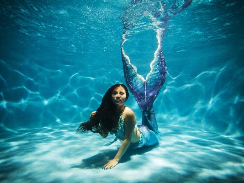 Mulher posa para foto, vestida de sereia, em uma piscina na cidade de Chongqing, na China