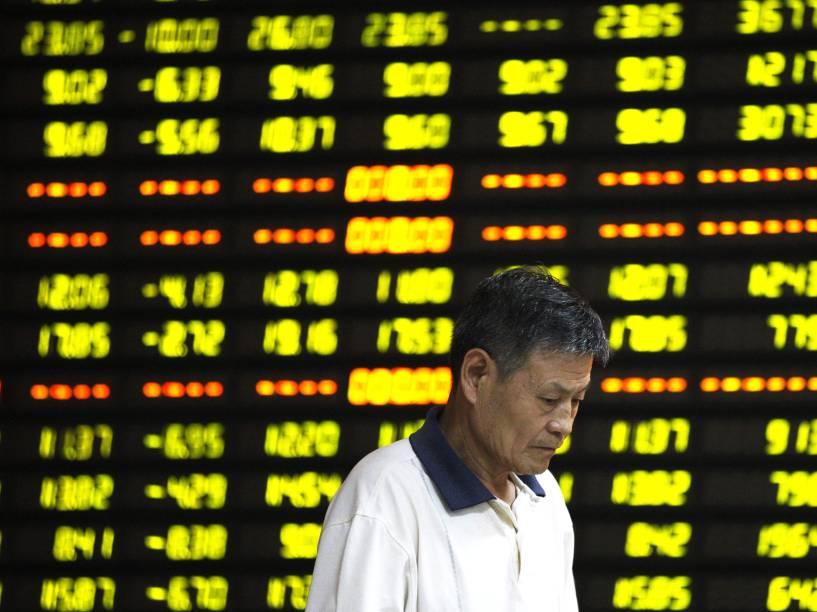 Investidor é visto em frente ao painel eletrônico com informações da bolsa, em uma corretora de Huaibei, na China. As ações no país caíram mais de 8%, sua maior queda em um dia em mais de oito anos - 27/07/2015