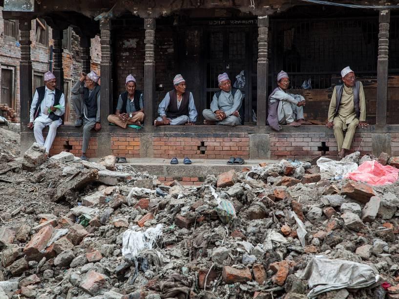 Grupo de idosos conversa perto de uma pilha de escombros em Bhaktapur, Nepal, três meses após o terremoto que atingiu o país - 29/07/2015