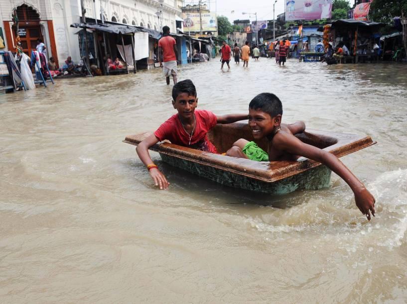 Crianças brincaram em uma rua inundada pela cheia do rio Ganges, em Calcutá, na Índia