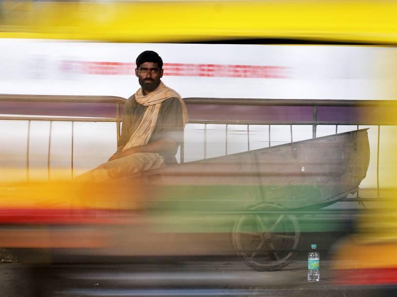 Carregador é fotografado enquanto aguarda clientes em um mercado na cidade de Bengaluru, na Índia - 04/08/2015