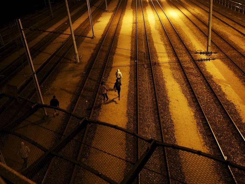Imigrantes correram depois de atravessar uma cerca enquanto tentam acessar o túnel da Mancha em Frethun, perto de Calais, na França