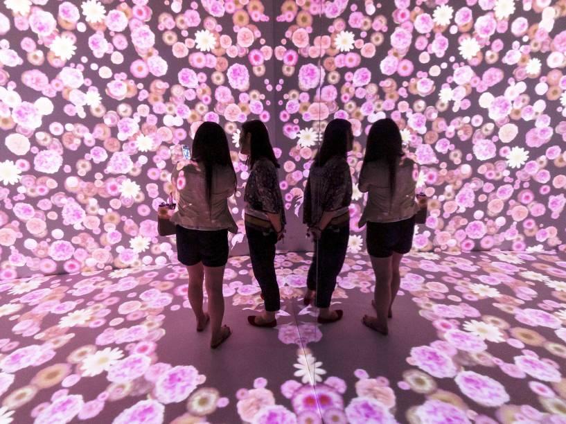 Visitantes observaram projeção de flores na parede e no chão de uma sala em um shopping de Xangai, na China