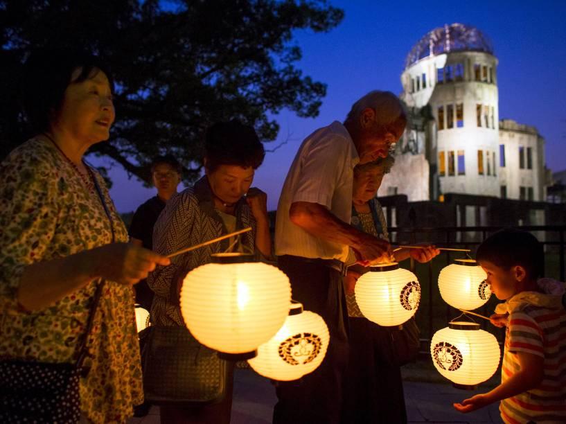 Moradores seguraram lanternas de papel em frente ao Domo da Bomba Atômica, durante cerimônia em memória às vítimas da bomba que atingiu Hiroshima, Japão