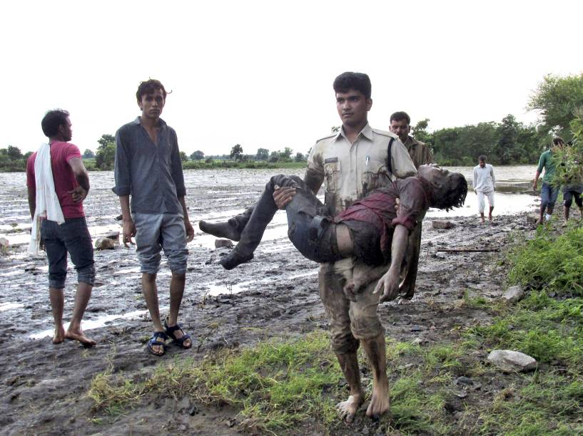 Policial carregou um passageiro no colo após acidente na cidade de Harda, em Madhya Pradesh, Índia. Pelo menos 24 pessoas morreram e outras mais de vinte ficaram feridas