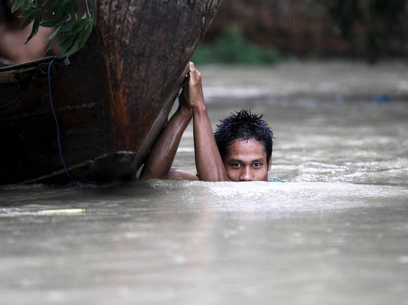 Jovem move seu barco em uma vila inundada em Irrawaddy, Myanmar - 06/08/2015