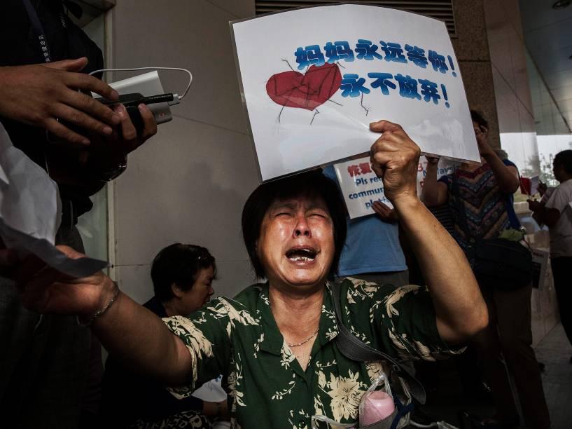 Parente de um passageiro do voo MH370 da Malaysia Airlines, desaparecido há mais de um ano, reage enquanto espera por informações do lado de fora do escritório companhia aérea em Pequim, na China - 06/08/2015