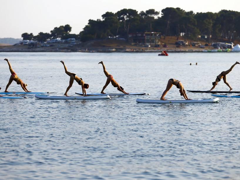 Pessoas praticam yoga sobre pranchas, na costa do mar adriático em Medulin, na Croácia - 06/08/2015