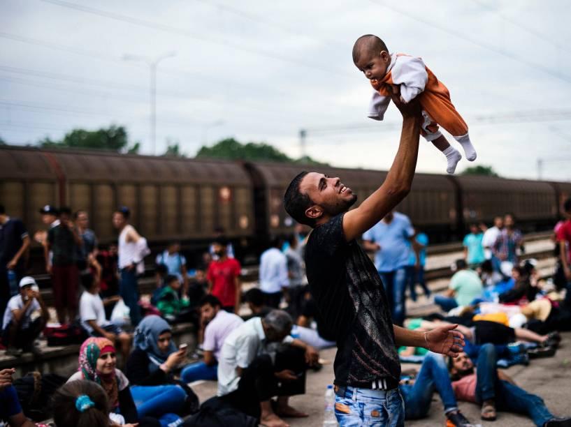 Imigrante levanta seu bebê enquanto espera um trem em direção à fronteira com a Sérvia na estação de Gevgelija, na Macedônia - 06/08/2015