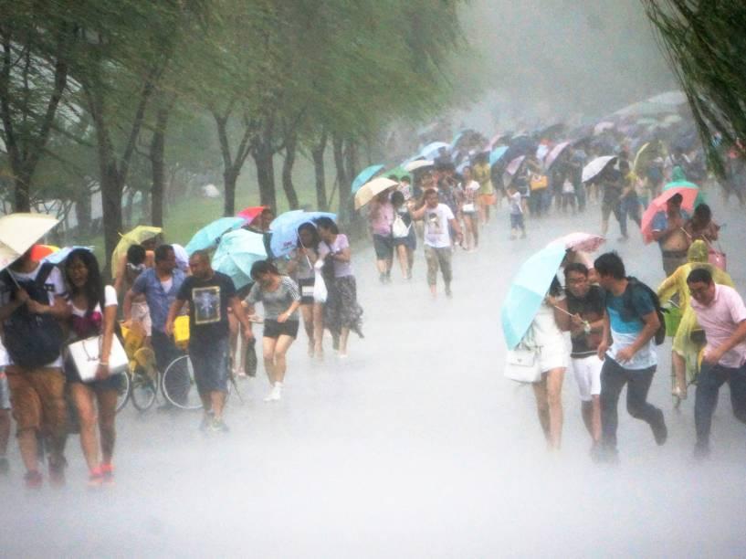 Chineses tentaram se proteger da chuva em meio a uma intensa ventania na cidade de Hangzhou, em Taiwan