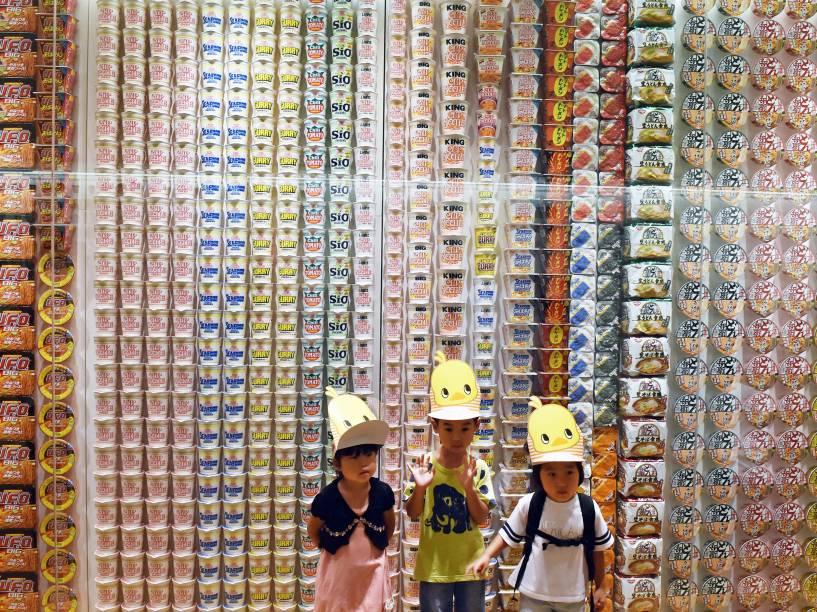 Crianças posam para foto em frente a um painel com pacotes de macarrão instantâneo de vários países no Museu Cup Noodle em Yokohama, no subúrbio de Tóquio - 13/08/2015