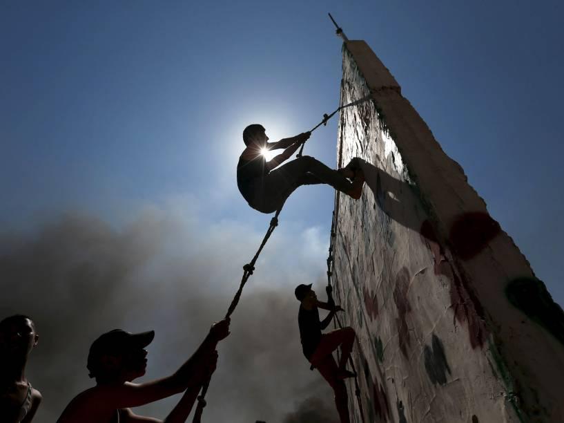 Jovens palestinos escalam uma parede durante exercício num acampamento de verão organizado pelo movimento Jihad Islâmica, em Khan Younis, sul da Faixa de Gaza - 13/08/2015