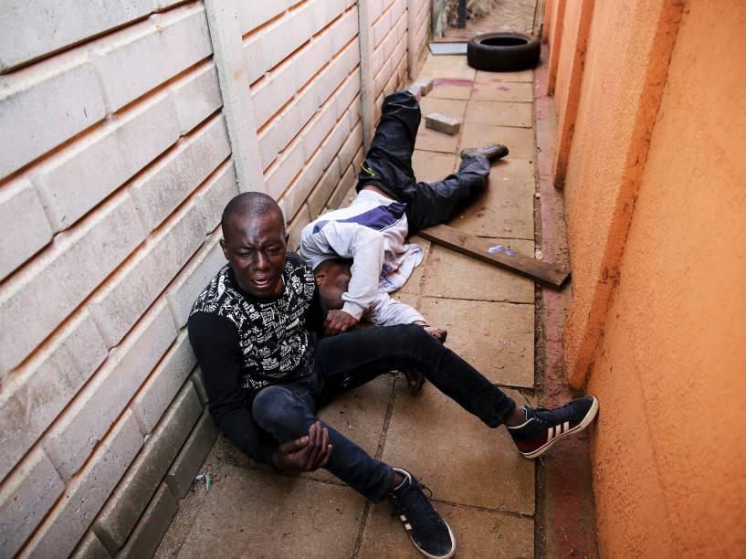 Suspeito se contorce de dor enquanto está algemado a seu cúmplice depois de ser baleado durante uma tentativa de invasão à casa de um casal de policiais, no sul de Johannesburgo, na África do Sul
