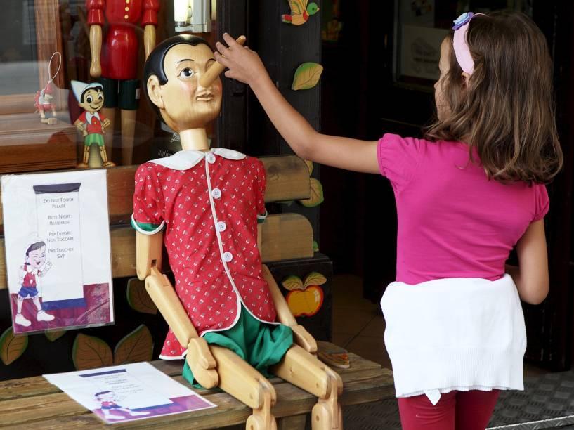 Menina brinca com um boneco Pinóquio em uma loja de Viena, Áustria - 21/08/2015