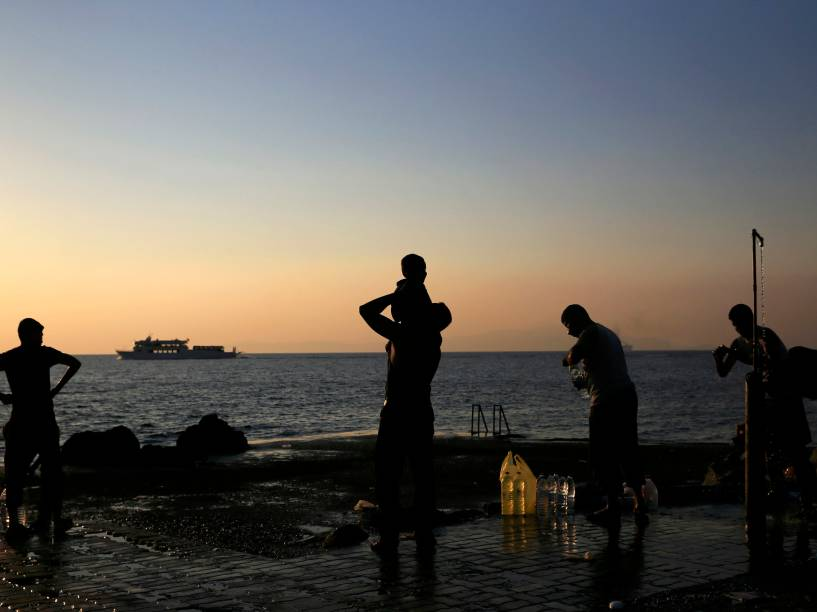 Migrantes são vistos durante o amanhecer na ilha grega de Lesbos, localizada no nordeste do mar Egeu - 21/08/2015