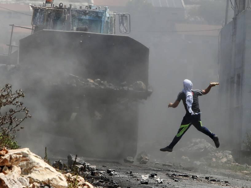 Manifestante palestino joga uma garrafa com tinta em uma escavadeira do exército israelense, durante confronto após protesto contra a expropriação da de terra Palestina por Israel - 21/08/2015