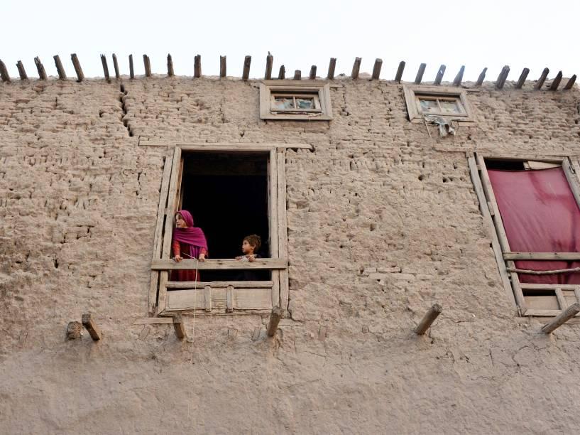 Crianças afegãs olham pela janela de uma casa nos arredores de Jalalabad - 03/09/2015