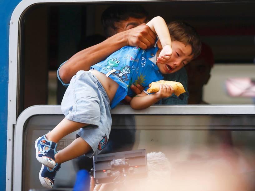 Imigrante puxa menino para dentro de um trem em uma estação de Keleti, em Budapeste, Hungria
