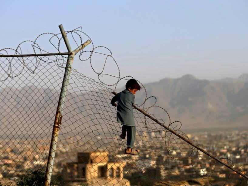 Garoto escala uma cerca enquanto brinca na cidade de Cabul, Afeganistão - 03/09/2015