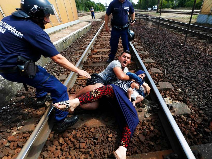 Família de refugiados se protege de policiais na estação ferroviária na cidade de Bicske, Hungria. A composição seguia para a fronteira com a Áustria.