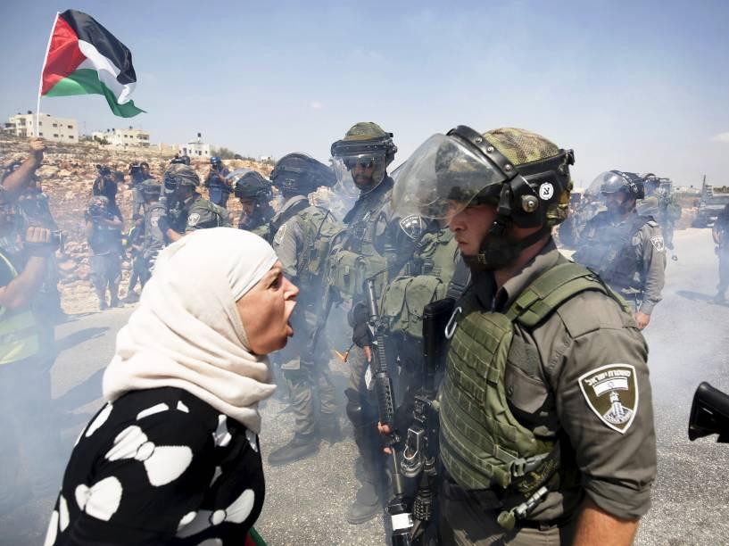 Mulher palestina discute com policial durante protesto na aldeia de Nabi Saleh, perto de Ramallah, Cisjordânia