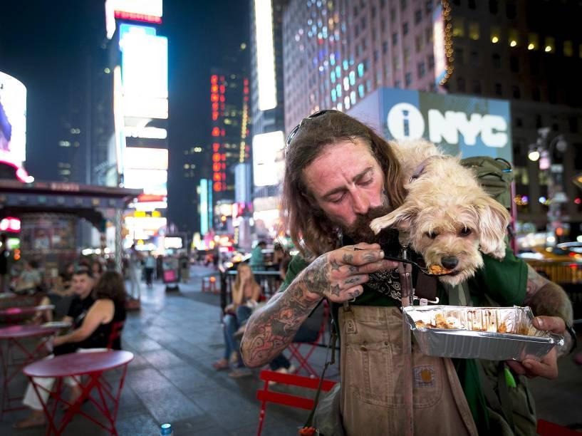 Deke Breuer dá pedaço de lasanha ao seu cão Cahlupa na Times Square, em Nova York. Breuer, que é de Detroit, está viajando pelo país e tem ensinado muitas coisas ao seu companheiro