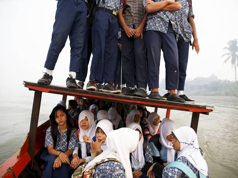 Estudantes se equilibram no teto de um barco durante travessia do rio Musi rumo à escola em Palembang, Indonésia 10/09/2015