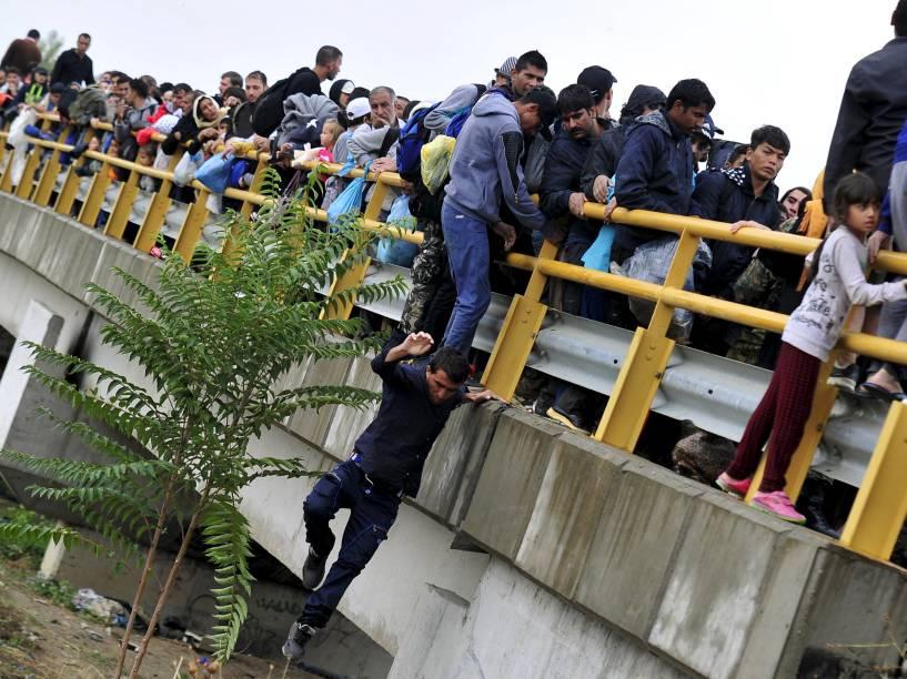 Homem pula de uma ponte enquanto tenta passar um bloqueio polícial junto a outros imigrantes, em Gevgelija, Macedônia. Ao estilo da Hungria, a Macedônia considera construir uma cerca para impedir o crescente fluxo de imigrantes vindos do sul - 10/09/2015