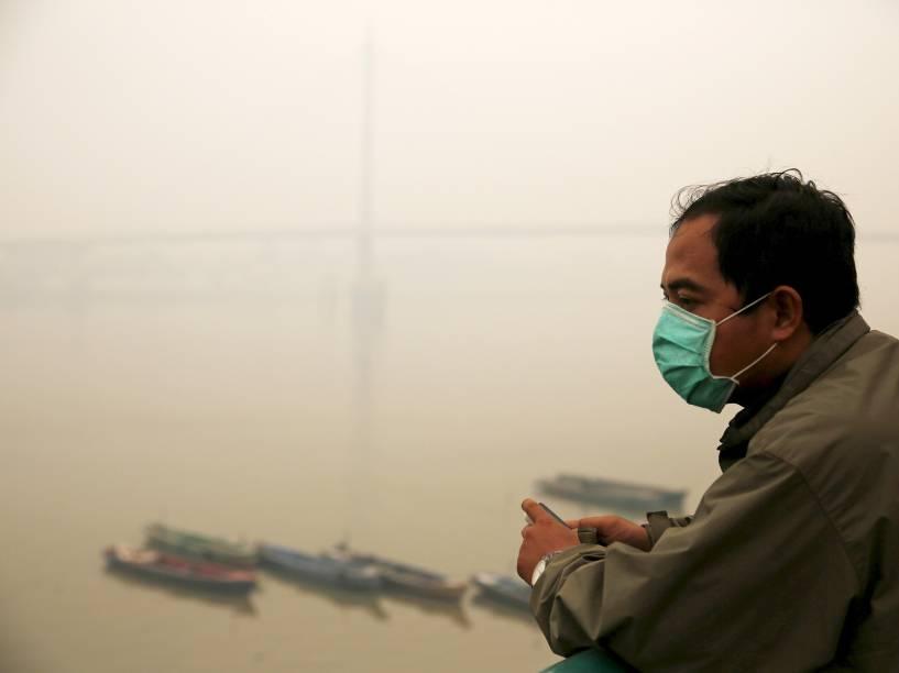 Homem usa máscara para se proteger do alto nível de poluição registrado em Jambi. A população da Indonésia vem sofrendo com a fumaça causada por queimadas florestais, o que obrigou o presidente do país, Joko Widodo, a anunciar que tomará medidas para amenizar o problema - 15/09/2015