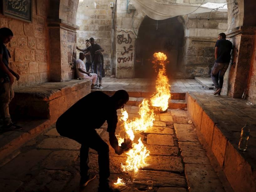 Manifestante palestino chuta um pneu em chamas durante confrontos com policiais israelenses na Cidade Velha de Jerusalém - 15/09/2015