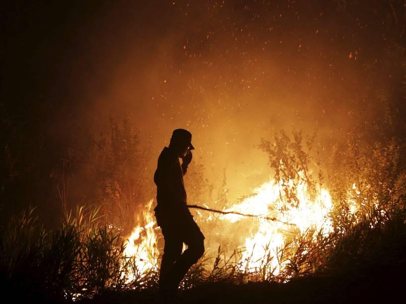 Oficial da agência local de Gestão de Calamidades (BPBD) tenta extinguir um incêndio na região da Sumatra Meridional, na Indonésia - 16/09/2015