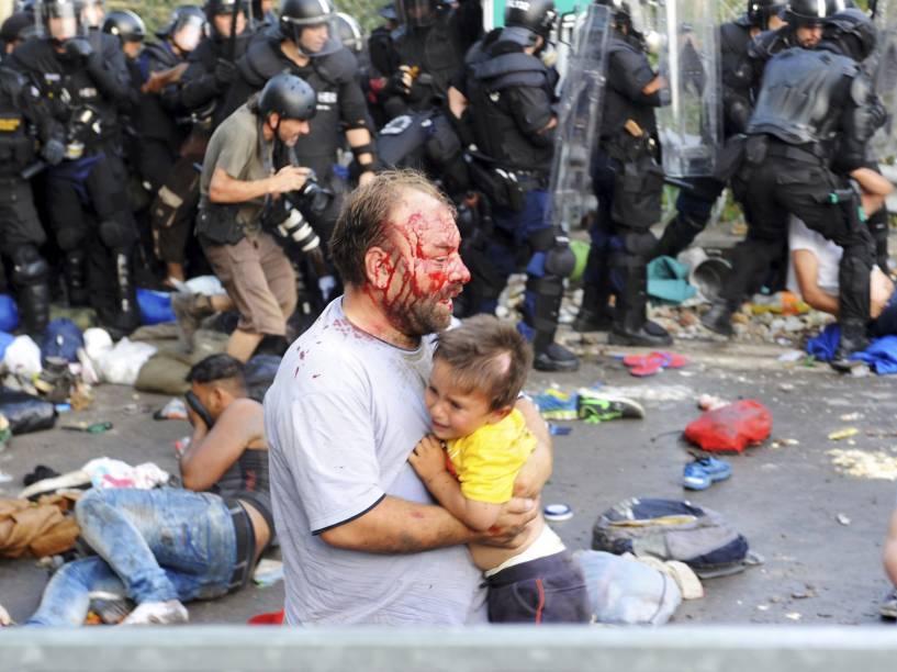 Homem ferido carrega uma criança durante confrontos entre refugiados e a polícia húngara na fronteira com a Sérvia em Röszke - 16/09/2015