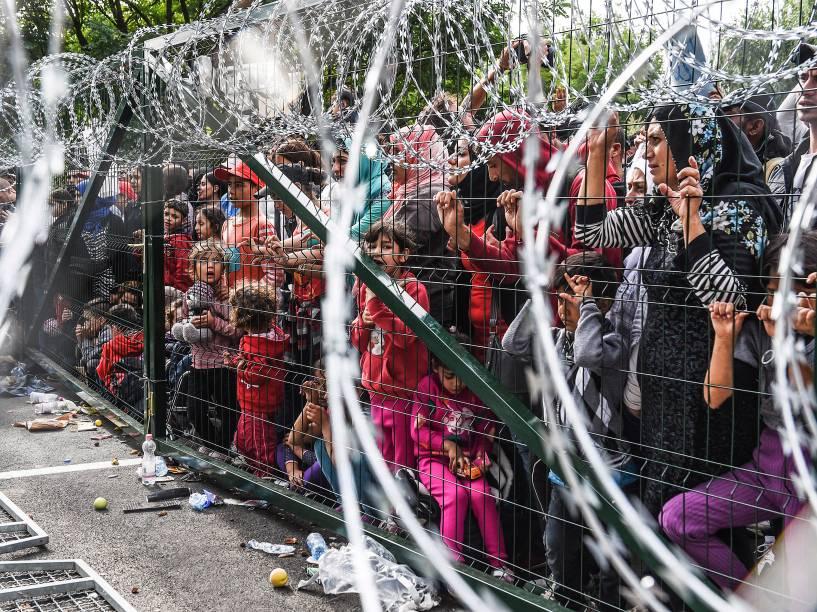 Refugiados ficam atrás de uma cerca de arame farpado na fronteira húngara com a Sérvia, perto da cidade de Horgos - 16/09/2015