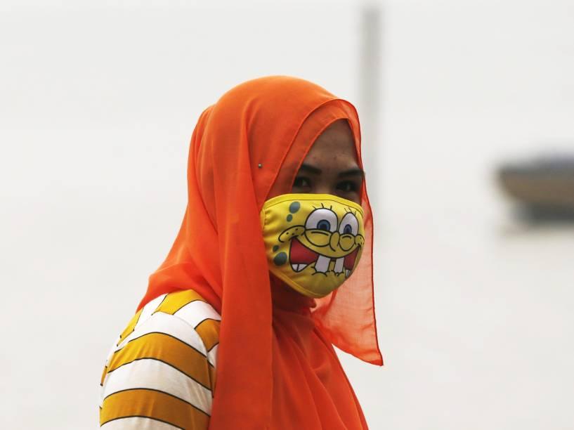 Mulher usa máscara para se proteger de atmosfera contaminada por fumaça de incêndios florestais em Jambi, província da Indonésia - 17/09/2015