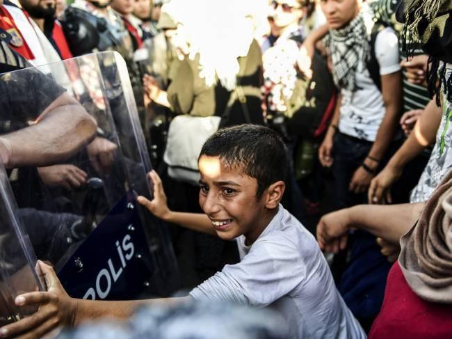 Garoto sírio empurra uma barricada policial enquanto refugiados marcham ao longo de uma estrada em direção à fronteira com a Grécia, na cidade turca de Edirne - 18/09/2015