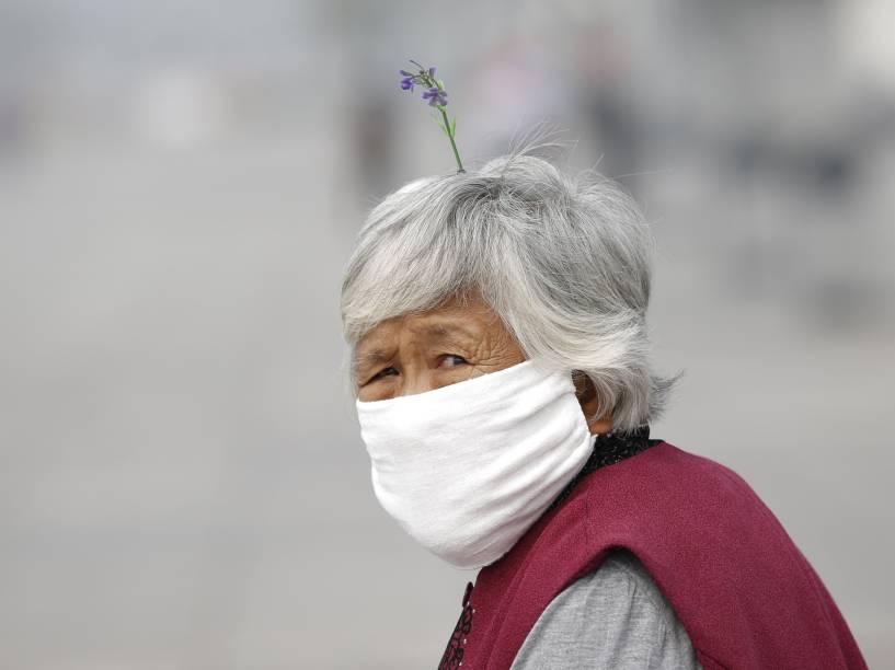 Mulher usa máscara durante dia nublado próximo ao Estádio Nacional de Pequim, China - 24/09/2015
