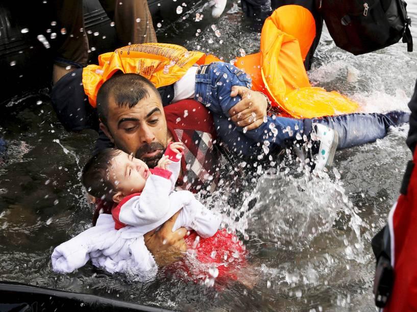 Refugiado sírio segura crianças enquanto se esforça para sair de um bote na ilha grega de Lesbos - 24/09/2015