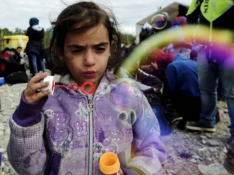 Menina refugiada soprou bolhas de sabão em um acampamento na cidade de Gevgelija, na Macedônia, após cruzar a fronteira com a Grécia