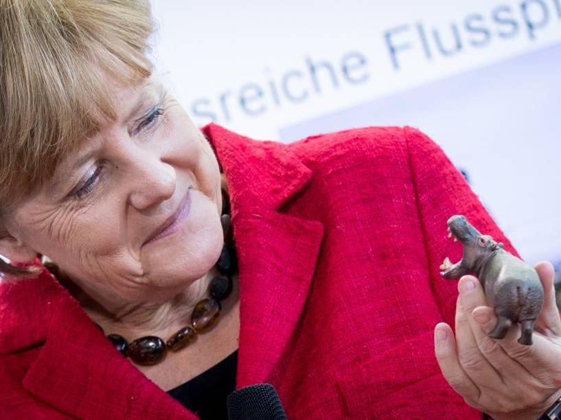 A chanceler alemã Angela Merkel segura um hipopótamo de brinquedo na chancelaria em Berlim, onde recebeu vencedores de uma competição de ciência para jovens
