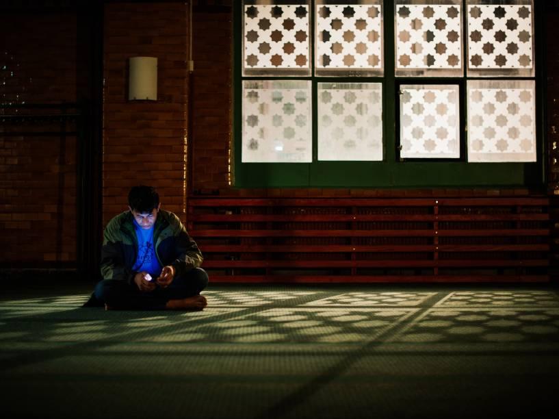 Refugiado verifica seu telefone na sala de oração da mesquita de Estocolmo, na Suécia