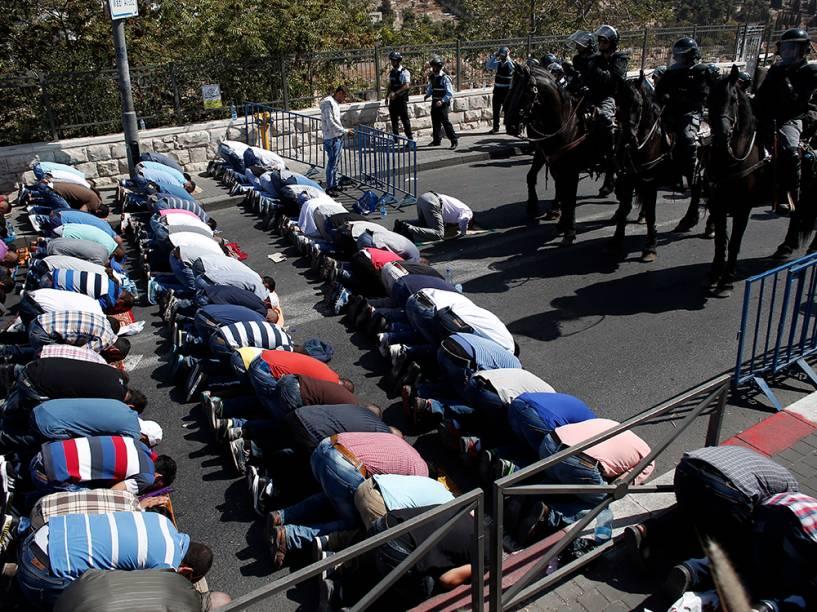 Palestinos fazem orações em frente a polícia israelense no bairro Wadi al-Joz, em Jerusalém. Uma restrição israelense proíbe que palestinos com menos de 40 anos de idade entrem na mesquita Al-Aqsa. O Conselho de Segurança da ONU vai realizar uma sessão especial para discutir a recente onda de violência entre israelenses e palestinos, que deixou 39 mortos ao longo das últimas duas semanas