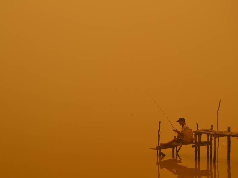 Pescador foi fotografado em meio a névoa ácida à beira de um rio na cidade de Palangkaraya, na Indonésia; incêndios florestais e agrícolas cobrem o sudeste da Ásia com uma nuvem