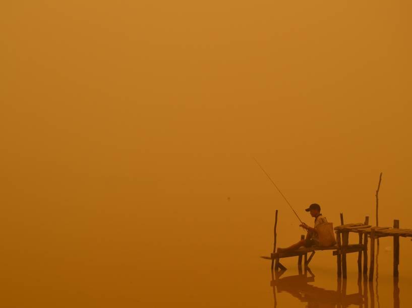 Pescador é fotografado em meio a névoa ácida à beira de um rio na cidade de Palangkaraya, na Indonésia; incêndios florestais e agrícolas cobrem o sudeste da Ásia com uma nuvem