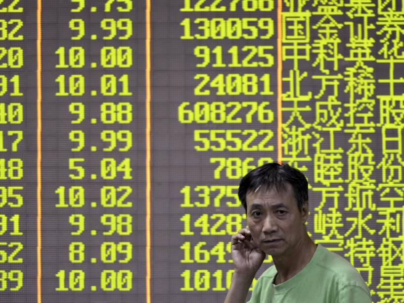 Investidor anda na frente de uma tela eletrônica que mostra informações em uma casa de corretagem em Hangzhou, China - 21/10/2015