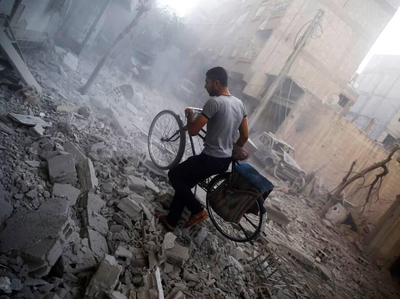 Sírio caminha entre destroços de prédios que ficaram totalmente destruídos após ataques em Douma, ao leste de Damasco - 21/10/2015